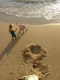Little girl on the beach. With a doll's pram and long afternoon shadows stock photography