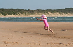 Little Girl on the beach. Little girl jumping mid air playing in the sand on the beach with a dirty face wearing sunglasses on her head Royalty Free Stock Image