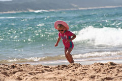 Little Girl on the beach. Little girl running and playing in the sand on the beach wearing a hat with waves behind her Stock Photography