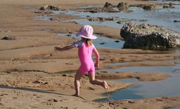 Little Girl on the beach. Little girl running and playing in the sand on the beach wearing a hat with tidal pools next to her Royalty Free Stock Images