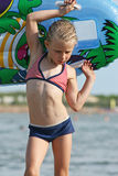 Little Girl on the beach. Girl with an inflatable surfboard stock photography