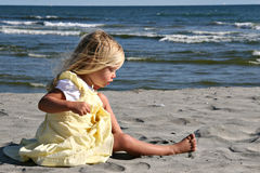 Little Girl on the beach. A little girl in a yellow dress discovers the sand Stock Photo