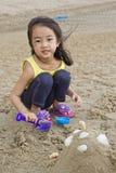 Little girl on the beach. Little girl building a sand castle on the beach Stock Photos
