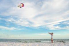 Little girl on the beach flying kite up high in the sky Stock Photos