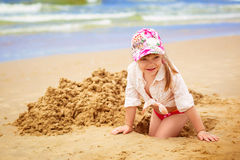 Little girl on the beach. The little girl at the beach gets out of the hole in the sand Stock Photography