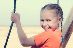 Little girl on the beach on a swing royalty free stock photography
