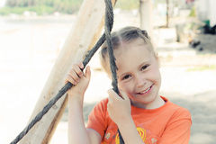 Little girl on the beach on a swing. Close up portrait royalty free stock photos