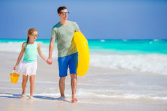 Little girl with beach toys walking along the sea with father. Family vacation. Stock Photos