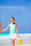 Little girl with beach toys walking along the sea with father Royalty Free Stock Photo