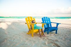 Little girl in beach wooden colorful chairs on Royalty Free Stock Images