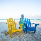 Little girl in beach wooden colorful chairs on Stock Images