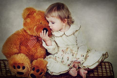 Little girl and bear Stock Photos