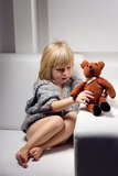 Little girl with bear on sofa Royalty Free Stock Photos