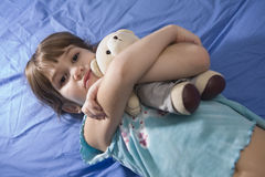 Little girl with bear on sofa Royalty Free Stock Photography
