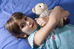 Little girl with bear on sofa Stock Photography