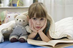 Little girl with bear on sofa Stock Images