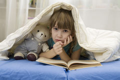 Little girl with bear on sofa Royalty Free Stock Image