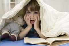 Little girl with bear on sofa Stock Photography