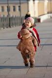 Little girl bears down the street Stock Photos