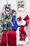 Little girl in a beautiful blue dress sits on a lap at Saint Nicolas Stock Photo