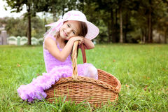 Little girl in a beautiful dress in a basket in a summer pa Royalty Free Stock Photography