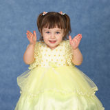 Little girl in beautiful dress claps his hands Royalty Free Stock Photos