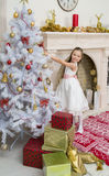 Little girl in  beautiful dress decorates the Christmas tree. X-mass and New year waiting and celebration concept. Holiday home decoration Royalty Free Stock Photos