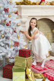 Little girl in  beautiful dress decorates the Christmas tree. X-mass and New year waiting and celebration concept. Holiday home decoration Royalty Free Stock Image
