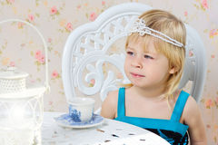 Little girl in a beautiful dress drinking tea. Little girl in a beautiful dress photography studio drinking tea Royalty Free Stock Photos