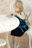 Little girl in a beautiful dress drinks tea. Little girl in a beautiful dress photography studio drinking tea Royalty Free Stock Photos