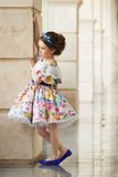 Little girl in a beautiful dress near wall outdoors. Fashion kid, fashionable concept Stock Photos