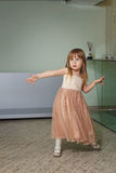 Little girl in a beautiful dress plays at home Stock Images