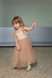 Little girl in a beautiful dress plays at home Stock Photos