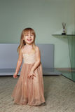 Little girl in a beautiful dress plays at home Royalty Free Stock Photos