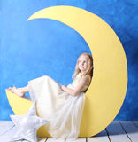 Little girl in a beautiful dress sits on a crescent moon. Her brilliant yellow dress. Girl dreamily looking up Royalty Free Stock Photos