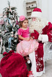 Little girl in a beautiful dress sits on a lap at Saint Nicolas Royalty Free Stock Image
