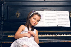 Girl in a beautiful dress sits at the piano Royalty Free Stock Images