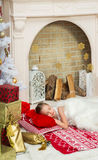 Little girl in  beautiful dress sleeps at home besides to Christ. Mas tree, waiting for Santa Claus.. X-mass and New year waiting and celebration concept Stock Images