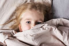 Little girl with beautiful eyes lying in bed. The baby is hiding under a blanket. stock photography