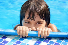 Little girl with beautiful eyes peeking out of the pool Stock Images