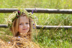 Little girl with beautiful face looks out of haystack Stock Image