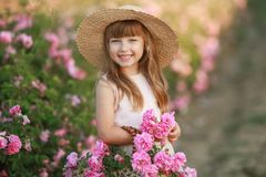 A little girl with beautiful long blond hair, dressed in a light dress and a wreath of real flowers on her head, in the stock photo