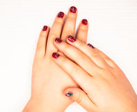 Little girl with beautiful manicure in dark pink. Towards white paper Stock Photos