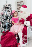Little girl in a beautiful pink dress sits on a lap at Saint Nicolas Stock Photography