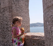 A little girl in a beautiful summer dress looking at the sea Stock Photo