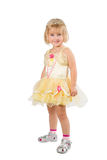 Little girl in a beautiful yellow dress and crown on white back Stock Photo