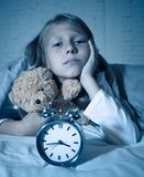 Little Girl in bed awake at night yawning and feeling restless showing clock she can not sleep. Cute sleepless little girl lying in bed showing alarm clock royalty free stock image