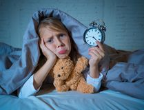 Little Girl in bed awake at night yawning and feeling restless showing clock she can not sleep royalty free stock image
