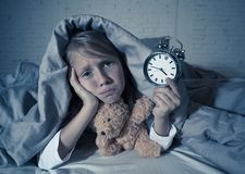 Little Girl in bed awake at night yawning and feeling restless showing clock she can not sleep. Cute sleepless little girl lying in bed showing alarm clock royalty free stock photos