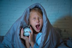 Little Girl in bed awake at night yawning and feeling restless showing clock she can not sleep. Cute sleepless little girl lying in bed showing alarm clock royalty free stock photo